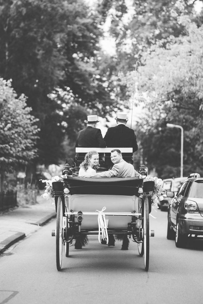 bruidspaar onderweg in de koets