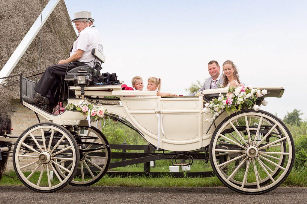 bruidspaar met bruidskinderen in koets
